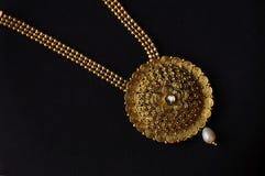 Konstgjord guld- halsband på en svart bakgrund arkivfoton