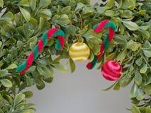 Konstgjord jul krans eller girland som göras av det plast- bladet som dekoreras av den röda och vita rottingen och det röda och g Arkivfoto