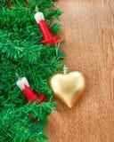 Konstgjord julgran, elkraftstearinljus och guld- hjärta Royaltyfri Foto