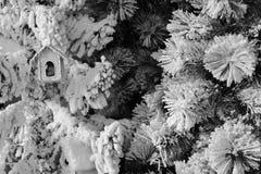 Konstgjord julgran med snö som dekoreras med jul tr arkivbild
