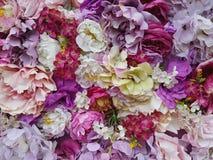 Konstgjorda blommor är olika skuggor av art: hel vägg, bakgrunden av ljusa blommor, gyckeln av våren Arkivfoto