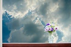 Konstgjorda blommor i en vas på en himmelbakgrund Arkivfoton