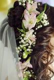 Konstgjorda blommor i håret den härliga gulliga frisyren låser model ståendeprofilbröllop royaltyfria bilder