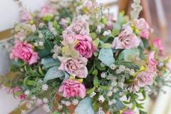 Konstgjorda blommor i korgen i tappningtema Arkivfoto