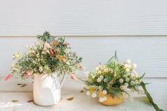 Konstgjorda blommor i korgen i tappningtema Arkivfoton