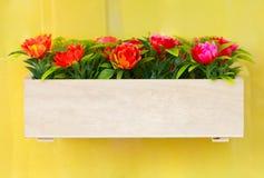 Konstgjorda blommor i träask. Arkivfoto