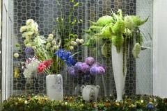 Konstgjorda blommor och växter i det glass fallet Arkivbild