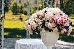 Konstgjorda blommor på gatan i den vita krukan Royaltyfri Foto