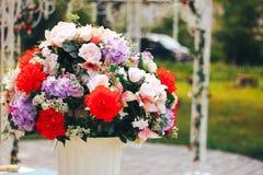 Konstgjorda blommor på gatan i den vita krukan Royaltyfria Bilder