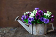 Konstgjorda blommor på trätabellen Fotografering för Bildbyråer