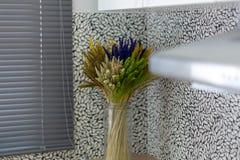 Konstgjorda blommor, purpurfärgat som är vita, bryner i klart exponeringsglas royaltyfri foto