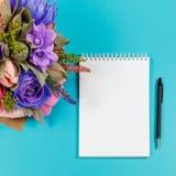 Konstgjorda handgjorda blommor, en anteckningsbok och en svart penna på en blå bakgrund Royaltyfria Bilder