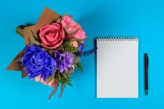 Konstgjorda handgjorda blommor, en anteckningsbok och en svart penna på en blå bakgrund Fotografering för Bildbyråer