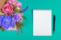 Konstgjorda handgjorda blommor, en anteckningsbok och en svart penna på en turkosbakgrund Arkivbild