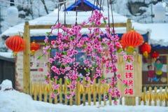 Konstgjorda körsbärsröda blommor på snöbyn royaltyfri bild