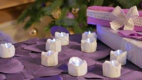 Konstgjorda stearinljus glöder på bakgrunden av julgranen arkivfilmer