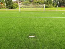 Konstgjort gräsfält på fotbolllekplats Detalj av ett kors av linjer i ett fotbollfält Plast- gräs- och jordningsgummi Royaltyfri Fotografi