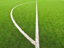 Konstgjort gräsfält på fotbolllekplats Detalj av ett kors av linjer i ett fotbollfält Plast- gräs- och jordningsgummi Royaltyfria Bilder