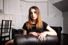 Konstig flicka, i sökande som aktivt placeras i svart läderstol Royaltyfri Fotografi