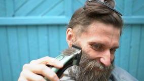 Konstig man med skägget som försöker att klippa för att äga hår med beskäraren arkivfilmer