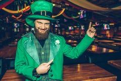 Konstig och lycklig ung man i grön dräktställning i bar- och punktbaksida Han ser på kamera och poserar Grabbkläder St Patrick arkivfoton