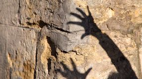 Konstig skugga av två händer på ett gammalt stenar väggen Svart skugga, kvinnlig hand arkivbild