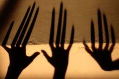 Konstig skugga p? v?ggen Ruskig skugga abstrakt bakgrund Svart skugga av en stor hand p? v?ggen Kontur av en hand på T royaltyfri fotografi