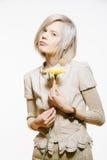 Konstig slank blond flicka med en gul blomma arkivbild