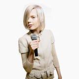 Konstig slank blond flickaallsångkaraoke arkivbilder