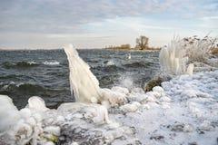 Konstiga isformer på kusten av en sjö under ett kallt pass i vinter royaltyfri bild