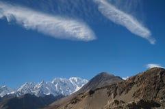 Konstiga moln över höga berg nära Passu, nordliga Pakistan Royaltyfri Foto