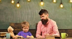 Konstkurs på dagiset Lärare och små ungehandstilbokstäver i förskriftsbok Gullig pojke som drar en bild med färgrikt royaltyfria bilder