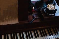 Konstlatte per koppen av varmt kaffe p? piano royaltyfri foto