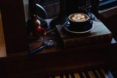 Konstlatte per koppen av varmt kaffe p? piano arkivbild