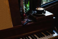 Konstlatte per koppen av varmt kaffe p? piano fotografering för bildbyråer