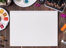 Konstnäråtlöje upp med borstar, pensils och tomt papper Arkivfoto