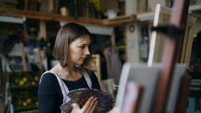 Konstnär för ung kvinna i förklädemålningbild på kanfas i konststudio arkivfoto