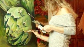 Konstnär för ung kvinna som arbetar i en studio som målar en kronärtskocka lager videofilmer