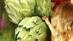 Konstnär för ung kvinna som arbetar i en studio som målar en kronärtskocka stock video