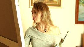 Konstnär för ung kvinna som arbetar i en studio som målar en kronärtskocka arkivfilmer