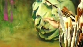 Konstnär för ung kvinna som målar en stor realistisk kronärtskocka stock video
