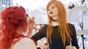 Konstnär med halloween makeup som applicerar halloween makeup på framsida för modell` s Royaltyfria Bilder