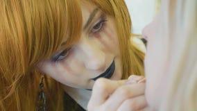 Konstnär med halloween makeup som applicerar halloween makeup på framsida för modell` s Royaltyfri Bild