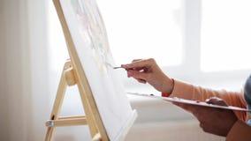 Konstnär med målning för palettkniv på konststudion lager videofilmer