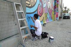 Konstnär Painting en vägg- vägg på en Vancouver gata arkivbild