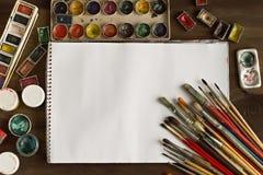 Konstnär` s borstar, målarfärger och albumet på träbakgrund Royaltyfri Bild