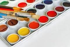 Konstnär` s borstar och målar på vit bakgrund Arkivfoto