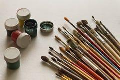 Konstnär` s borstar och målar på vit bakgrund Arkivbilder