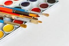 Konstnär` s borstar och målarfärger som isoleras på vit bakgrund Royaltyfri Foto