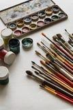 Konstnär` s borstar och målarfärger som isoleras på vit bakgrund Arkivfoton